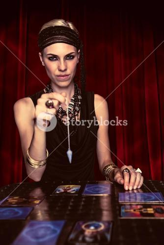 Composite image of fortune teller forecasting the future with pendulum