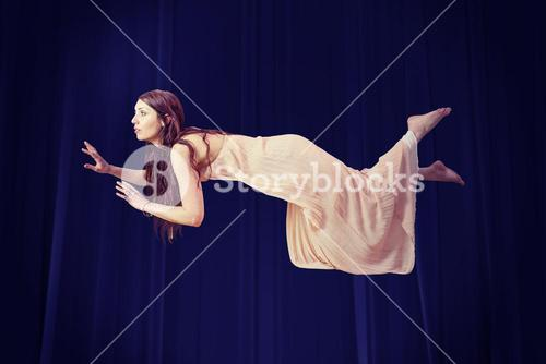 Composite image of full length of woman levitating