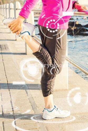 Composite image of sporty woman stretching leg at promenade