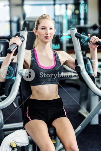Composite image of fit woman using exercise machine