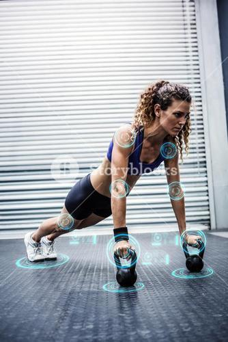 Composite image of muscular woman doing push-ups with kettlebells