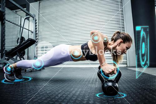 Composite image of muscular woman doing pushups with kettlebells