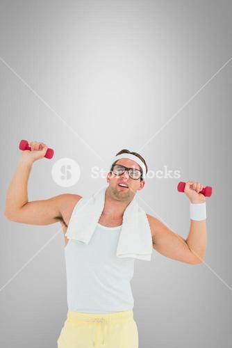Composite image of geeky hipster lifting dumbbells in sportswear