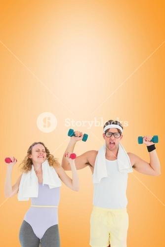 Composite image of geeky hipster couple lifting dumbbells in sportswear