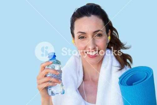 Composite image of fit beautiful brunette looking at camera while listening music
