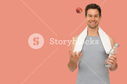 Composite image of smiling fit young man with apple and water bottle