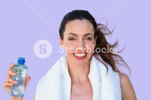 Composite image of beautiful brunette holding bottle of water