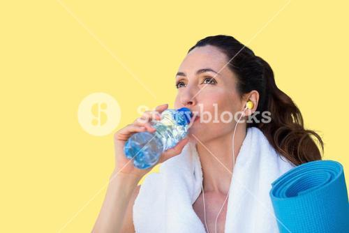 Composite image of fit beautiful brunette drinking water while listening music