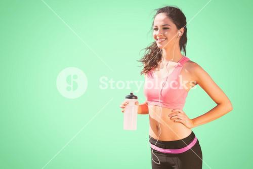 Composite image of beautiful smiling healthy woman holding water bottle