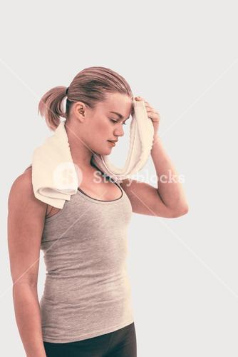 Composite image of muscular woman wiping herself with towel