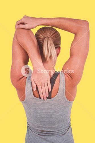 Composite image of rear view of muscular woman stretching her arm