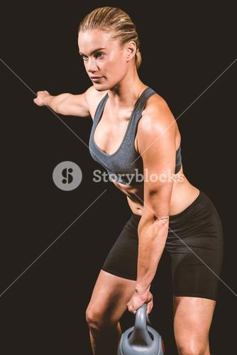 Composite image of muscular woman swinging heavy kettlebell