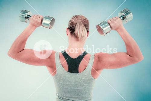 Composite image of  muscular woman working out with dumbbells