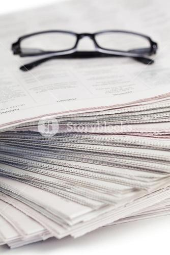 A pair of glasses on a pile of newspapers