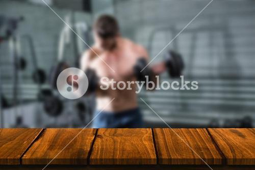 Composite image of concentrated muscular man lifting dumbbells
