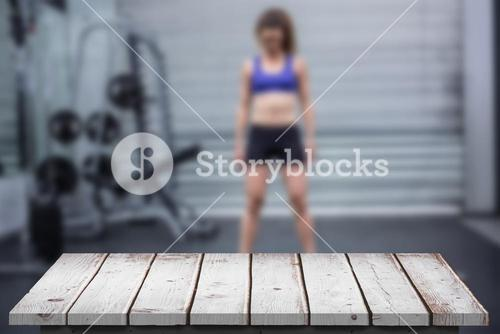 Composite image of muscular woman with barbell