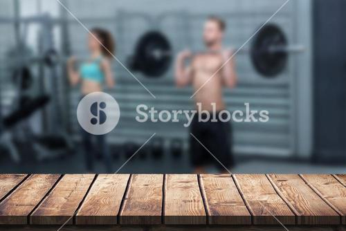 Composite image of muscular couple lifting weight together