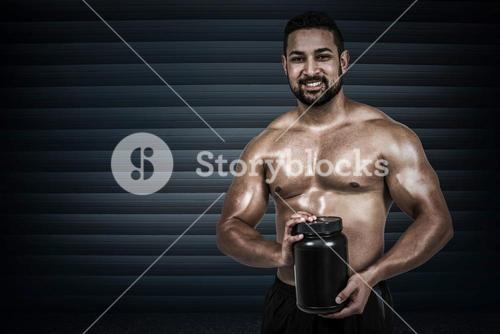 Composite image of muscular man with protein powder