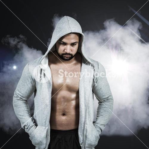 Composite image of muscular man in hooded jumper