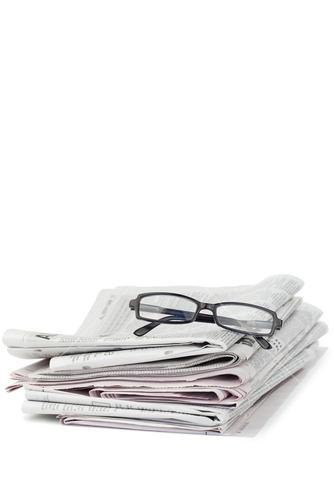 A pair of reading glasses on top of a pile of newspapers