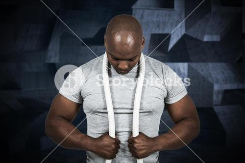 Composite image of fit man with battle rope