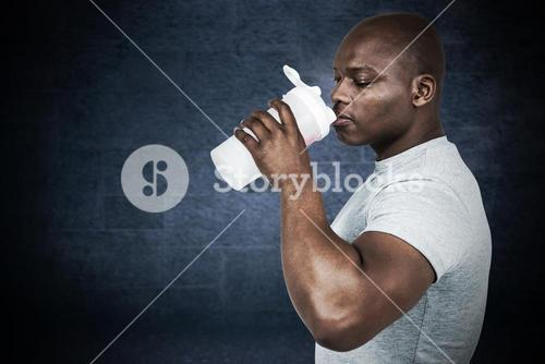 Composite image of fit man with protein shake