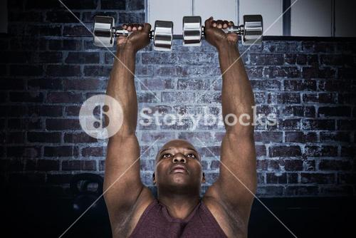 Composite image of fit man exercising with dumbbells