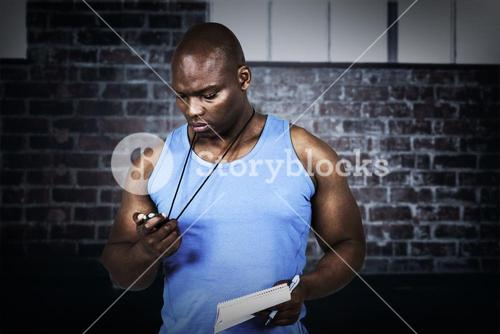 Composite image of fit trainer checking his stopwatch