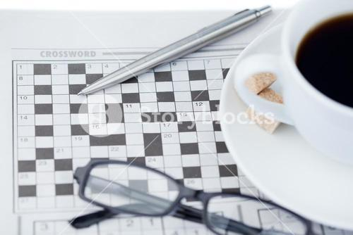 A cup of coffee a pen a pair of glasses and a crossword puzzle