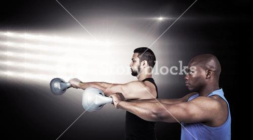 Composite image of strong friends lifting kettlebells together