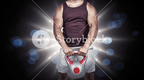 Composite image of muscular serious man holding a kettlebell