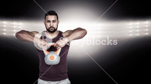 Composite image of muscular serious man lifting a kettlebell