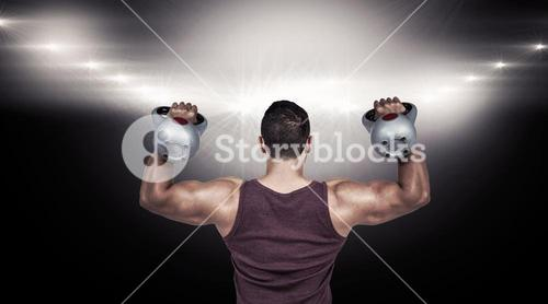 Composite image of rear view of a muscular man lifting kettlebells