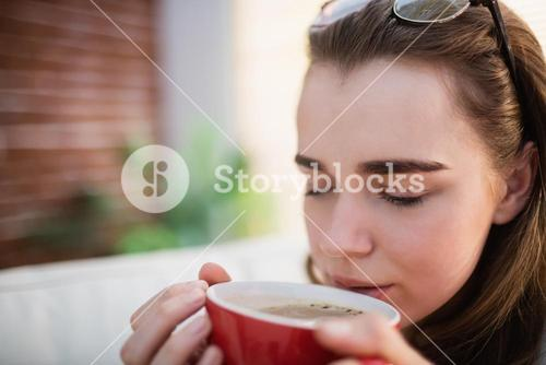 Pretty woman relaxing on couch with coffee