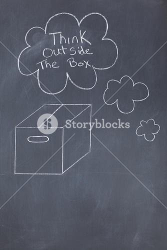 Close up of a blackboard with think outside the box written on it