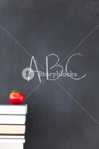 An apple some books and a blackboard