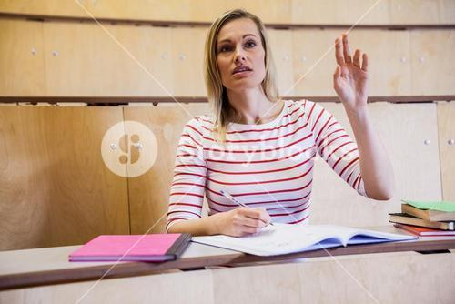 Female student raising a hand in class