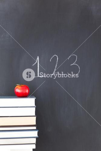 Books with a red apple and a blackboard