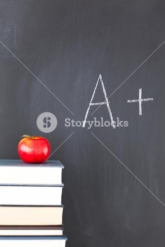 Books with a red apple and a blackboard with