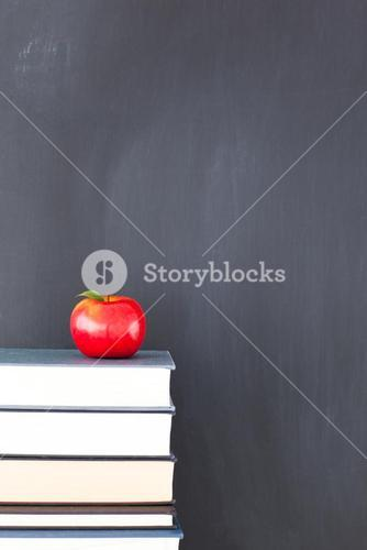 A red apple on a stack of books and a clean blackboard