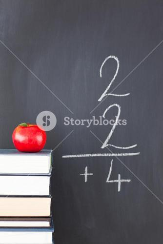 A simple addition on a blackboard and an apple and some books