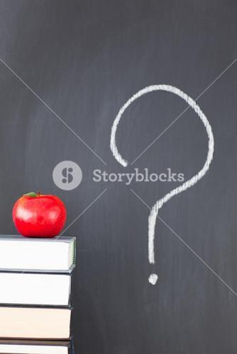 Stack of books with a red apple and a blackboard with a question mark symbol