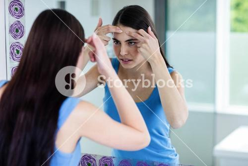 Unhappy woman with skin irritation cleaning her face