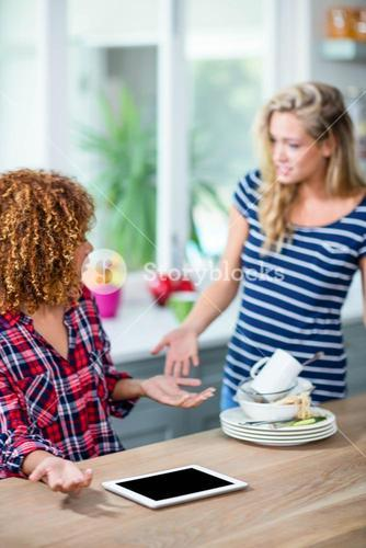 Upset woman showing dirty dishes to friend