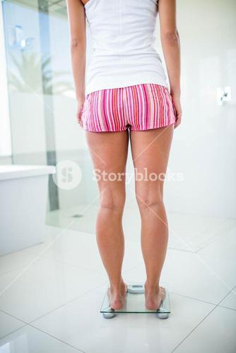 Rear view of woman on weighting scale