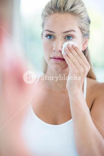 Woman wiping her face with cotton pad