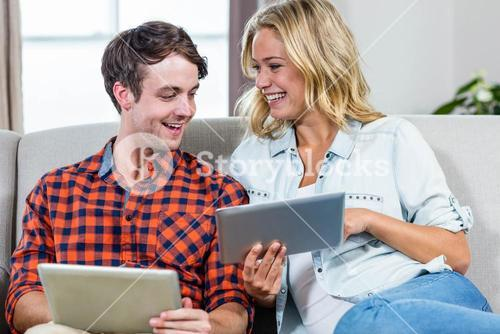 Couple using tablet computers