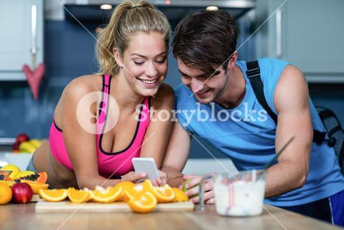 Healthy couple looking at smartphone
