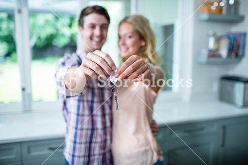 Cute couple showing their new home keys