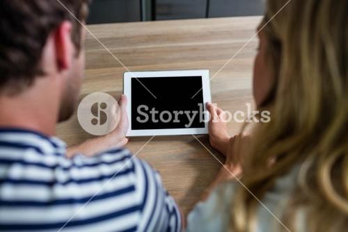 Focused couple using tablet